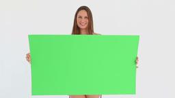 Woman in a bikini holding a blank poster Footage