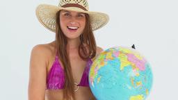 Woman in a bikini spinning a globe Footage