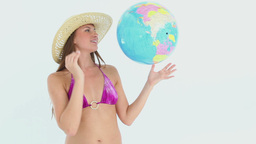 Woman in a bikini playing with a earth ball Stock Video Footage