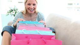 Happy woman looking into her shopping bags Footage