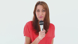 Brunette haired woman singing in a microphone Footage