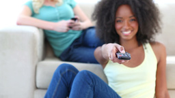 Black woman watching TV while a friend is on a cou Stock Video Footage