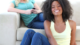 Black woman watching TV while a friend is on a cou Footage