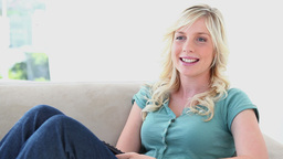 Blonde haired woman laughing in front of her TV Stock Video Footage