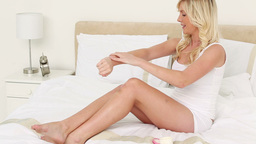 Blonde woman applying cream on her body Stock Video Footage