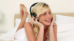 Blonde haired woman listening to music Footage
