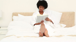Black haired woman reading a book in bathrobe Footage