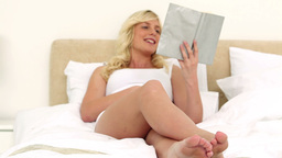 Young blonde woman reading a book Stock Video Footage