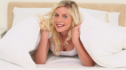 Young blonde woman under her blanket Footage