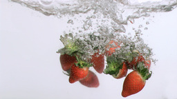 Strawberries in super slow motion falling in the w Footage