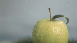 Drops falling in super slow motion on a green appl Stock Video Footage