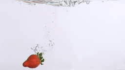 Red fruit in super slow motion falling in the wate Footage