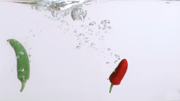 Red and green peppers in super slow motion diving Footage