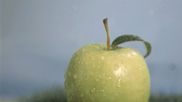 Apple in super slow motion receiving raindrops Footage