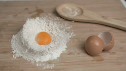 Egg in super slow motion being placed on flour Footage