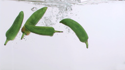 Four peppers in super slow motion falling in the water Footage