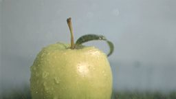 Green apple in super slow motion put under the rai Stock Video Footage