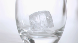 Ice cubes in super slow motion being put in a glas Footage