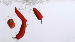 Red peppers in super slow motion splashing Footage