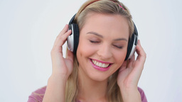Smiling blonde woman listening to music Footage