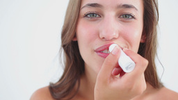 Smiling woman using lip balm for her lips Live Action