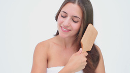 Smiling woman brushing her brown hair Stock Video Footage