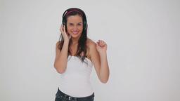 Smiling brunette listening to music on headphones Footage