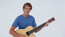 Smiling brunette man playing the guitar Footage