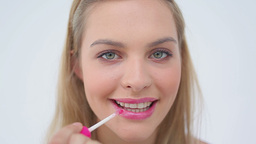 Happy woman using a lip brush Footage