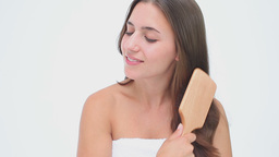 Smiling woman brushing her long hair Footage