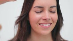 Hairdresser using hair spray on a brunette woman Footage