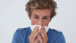 Sick man sneezing into a tissue Stock Video Footage