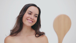 Happy brunette woman looking at a hand mirror Footage