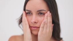 Peaceful brunette woman massaging her cheeks Footage