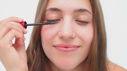 Joyful brunette applying mascara on her eyelashes Footage