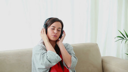 Happy brunette woman sitting while listening to mu Footage