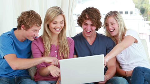 Happy friends laughing in front of a laptop Footage