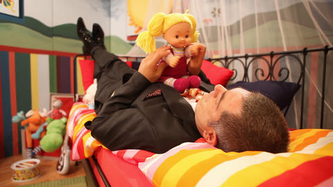 Mature man playing with doll Stock Video Footage