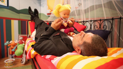 Mature man playing with doll Footage