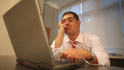 Sleepy businessman using laptop in office Stock Video Footage