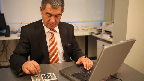 Businessman working on laptop in office, calculating Stock Video Footage