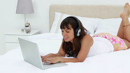 Smiling woman using a laptop while wearing headpho Stock Video Footage