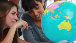 Smiling students pointing at countries on a globe Stock Video Footage