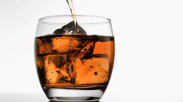Glass filled in super slow motion with whiskey Stock Video Footage