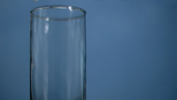 Milk flowing in super slow motion in a glass Stock Video Footage