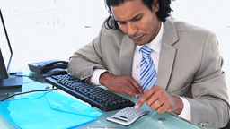 Businessman using a calculator to check numbers on Footage