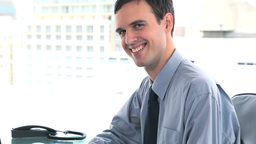 Businessman looking at camera while sitting at his Footage