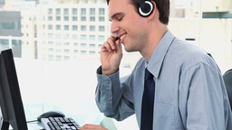 Businessman working with a computer and a headset Footage