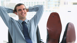 Happy businessman with his feet on a desk Footage