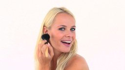 Blonde applying powder on her face Footage